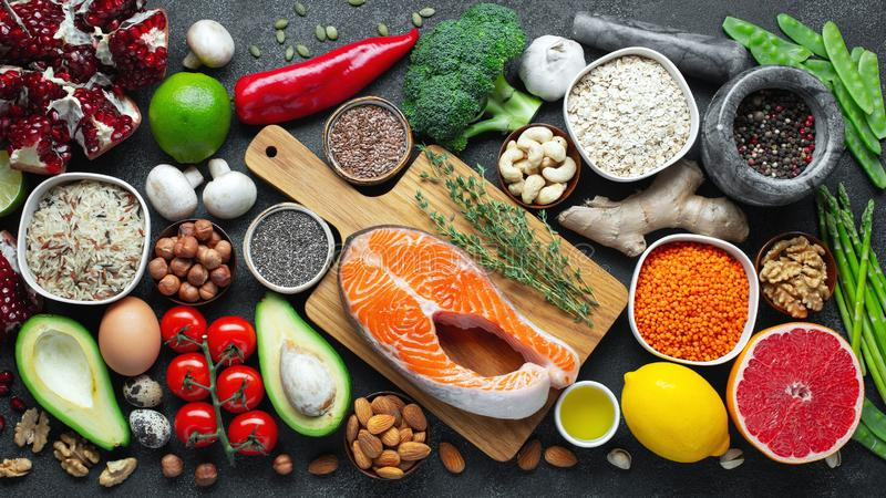 Выбор еды здоровой еды чистый: рыбы, плод, гайки, овощ, семена, superfood, хлопья, овощ лист на черном бетоне стоковая фотография