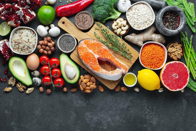Выбор еды здоровой еды чистый: рыбы, плод, гайки, овощ, семена, superfood, хлопья, овощ лист на черном бетоне стоковая фотография rf