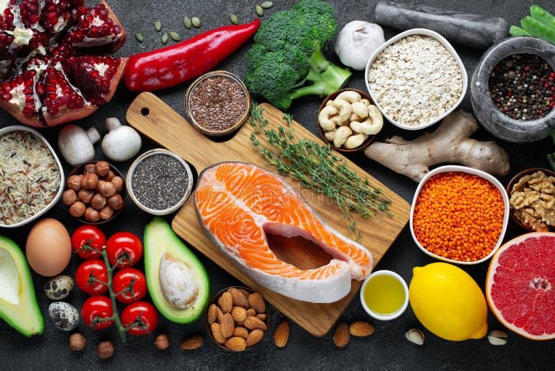 Выбор еды здоровой еды чистый: рыбы, плод, гайки, овощ, семена, superfood, хлопья, овощ лист на черноте стоковые изображения
