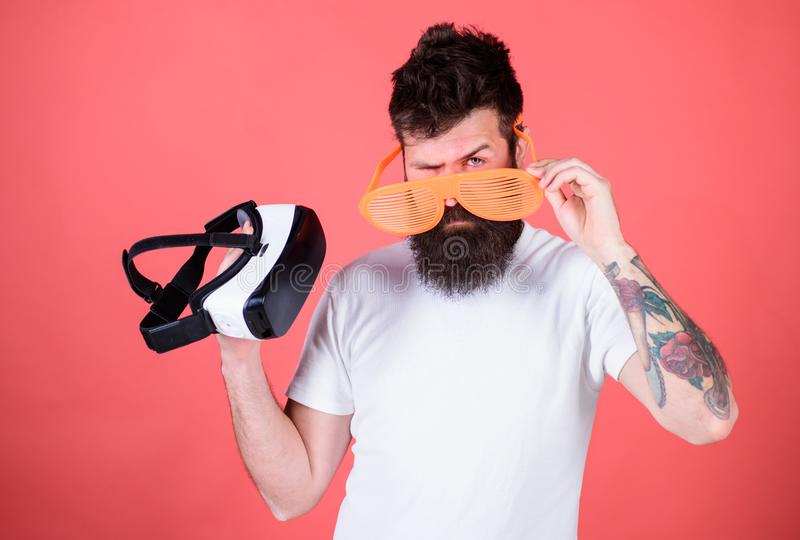 Выбор между реальностью и VR Укомплектуйте личным составом бородатый битника с шлемофоном виртуальной реальности и louvered солне стоковое изображение