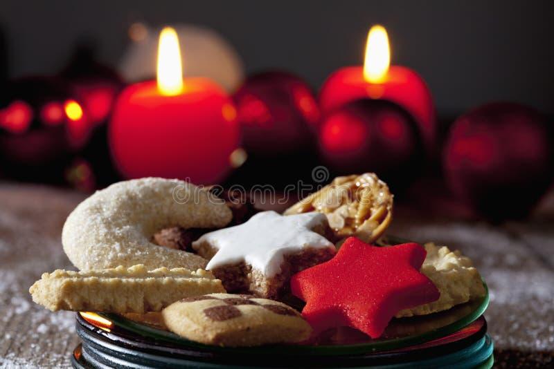 Выбор печений рождества на плите на свечах деревянного пола горящих в предпосылке стоковая фотография