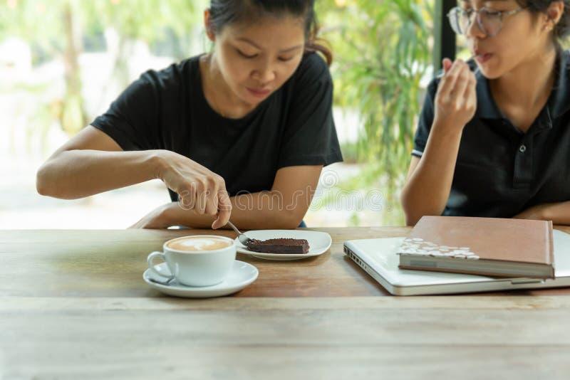 Выбранные друзья foceus женские наслаждаются иметь торт пирожного в кофейне стоковое фото
