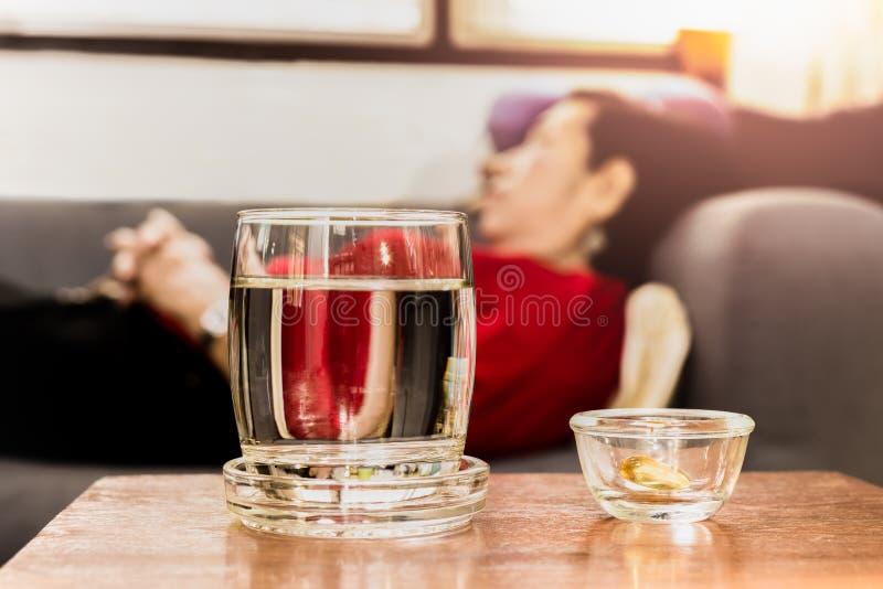 Выбранный фокус на пилюльках с стеклом воды на таблице с старшием стоковое фото