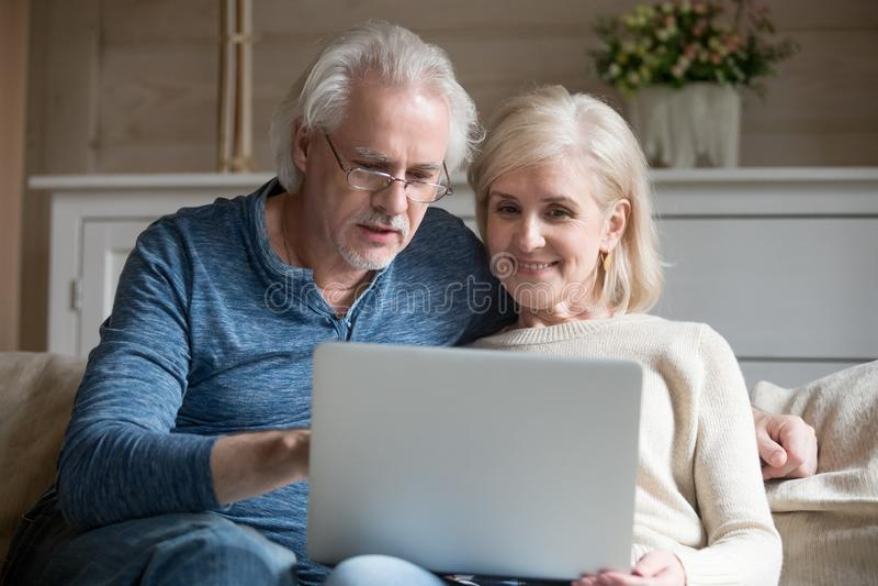 Выбытые старые пары используя компьтер-книжку совместно говоря сидеть на софе стоковое фото