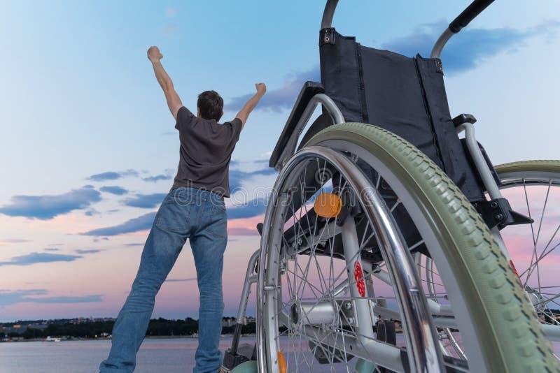 Выведенный из строя с ограниченными возможностями человек здоров снова Он счастлив и стоящ около его кресло-коляскы стоковые изображения rf