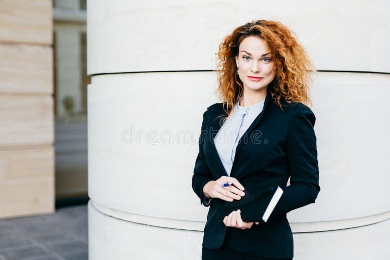 выглядящая Приятн курчавая женщина одела официально, держащ тетрадь в руках, идя иметь острословие встречи ее деловые партнеры Go стоковые изображения rf