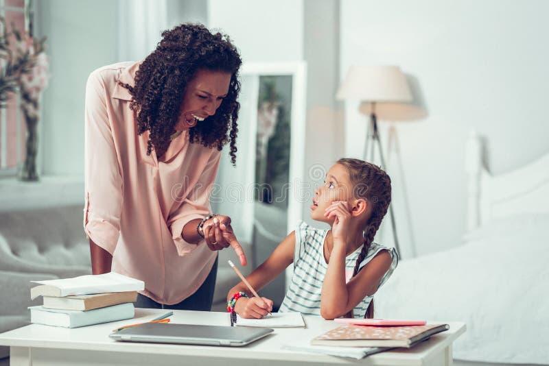 выглядящая Славн мать выкрикивая на небольшой сотрясенной милой дочери стоковая фотография rf