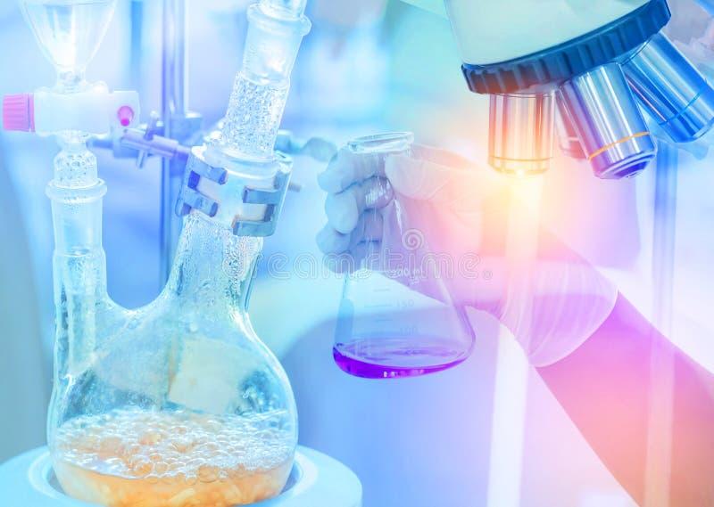 Выгонка установленная с капельными воронками отделяет компонентные вещества от жидкостной смеси при ученый руки держа flas стоковое фото