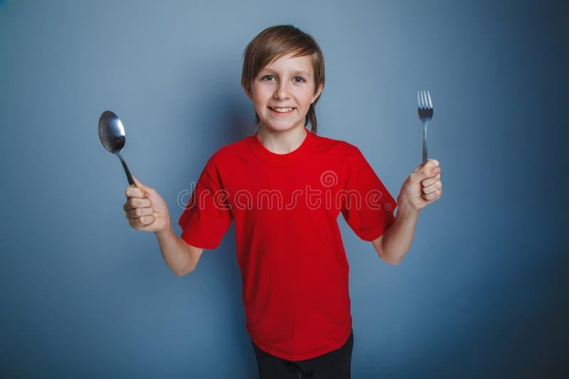 выглядящий Европейск мальчик 10 лет держа ложку стоковое фото
