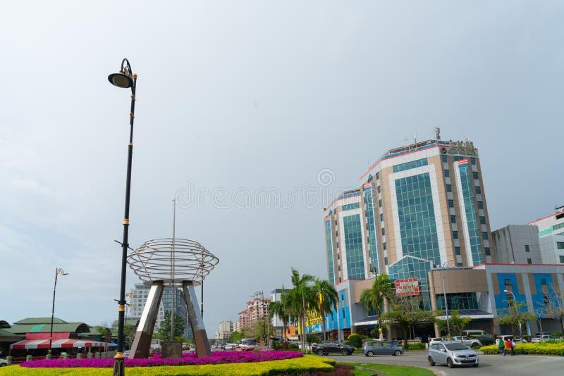 Выдающее искусство публики нержавеющей стали, скульптура на карусели корабля в Kota Kinabalu с красочными садами и фоном города стоковые изображения rf