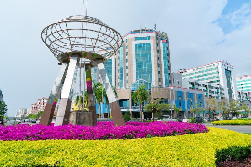 Выдающее искусство публики нержавеющей стали, скульптура на карусели корабля в Kota Kinabalu с красочными садами и фоном города стоковая фотография rf