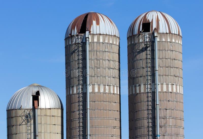 Выдержанные силосохранилища против голубого неба в сельских Соединенных Штатах стоковые фотографии rf