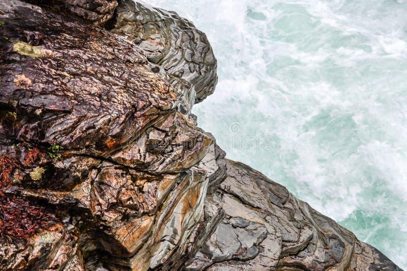 Выдержанный камень вдоль быстроподвижного реки в национальном парке ледника стоковая фотография