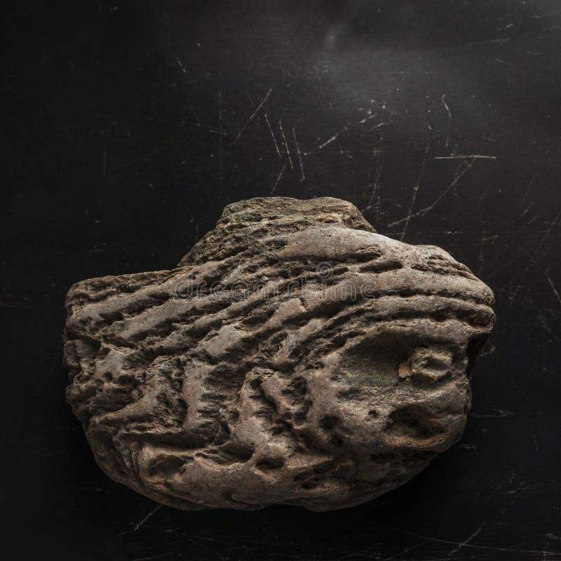 Выдержанный утес на темной поцарапанной предпосылке Легендарный артефакт концепции символа силы, смелости и излечивать стоковая фотография rf