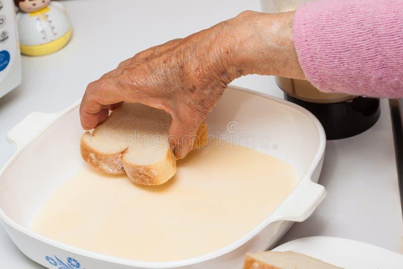 Выдерживая хлеб в смешивании для подготовки французской здравицы стоковые фото