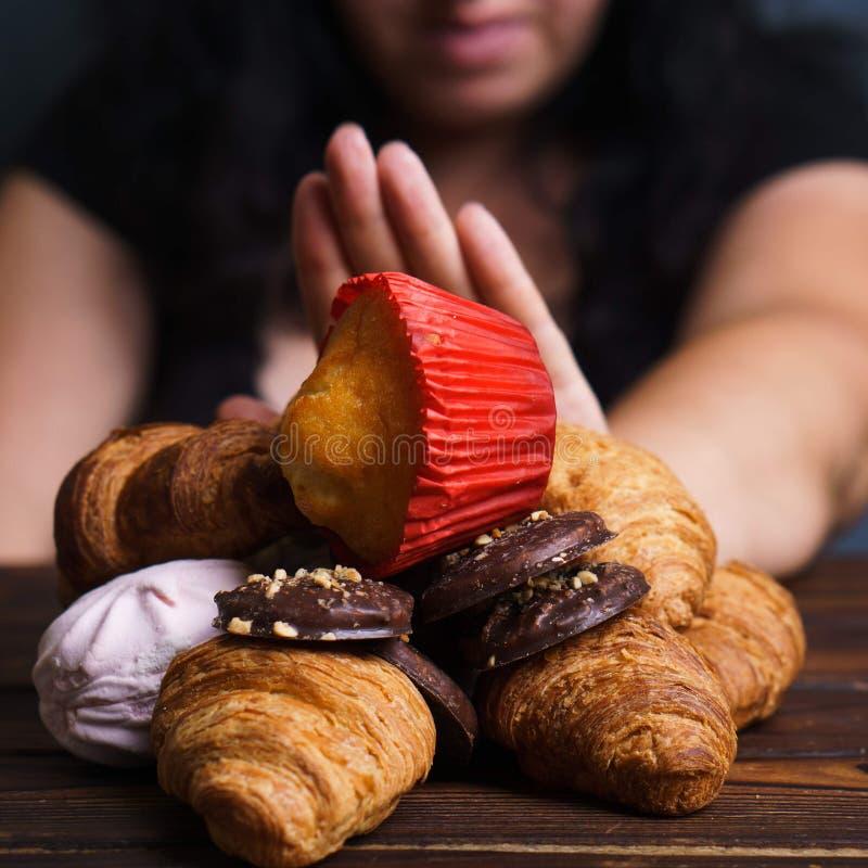 Выжимк молодой женщины есть высококалорийную вредную пищу стоковая фотография rf
