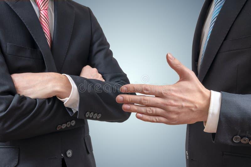 Выжимк рукопожатия Человек отказывает руку встряхивания с бизнесменом который предлагает его руку стоковое фото