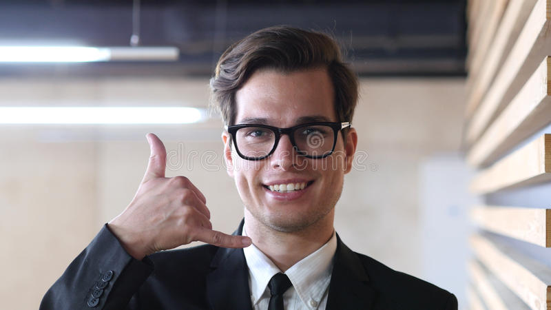 Вызовите меня, жест молодым бизнесменом стоковое фото