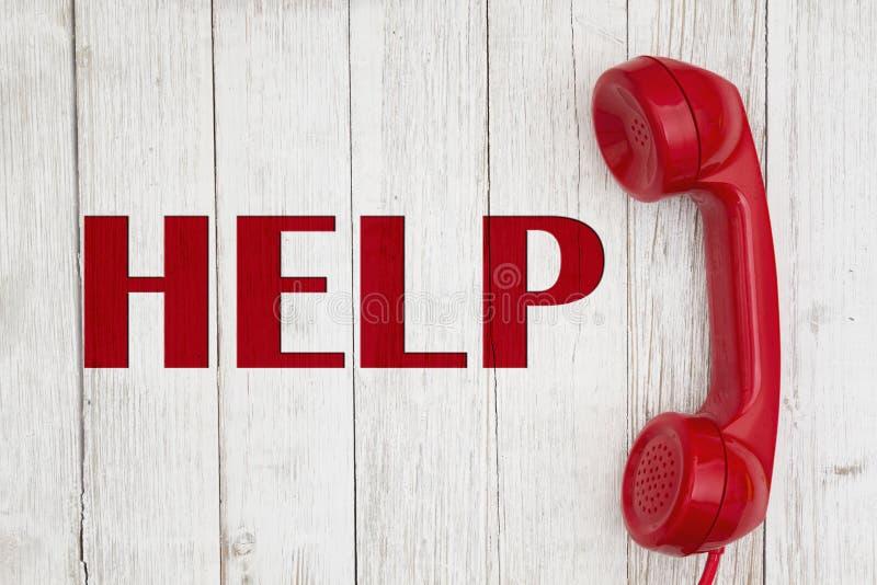 Вызывать для сообщения помощи с ретро красной телефонной трубкой телефона на выдержанной древесине побелки стоковая фотография