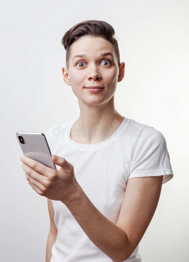 Выигрыш счастливой смешной тысячелетней женщины празднуя или победа, триумф, держа телефон Жизнерадостная возбужденная девушка, с стоковое изображение rf