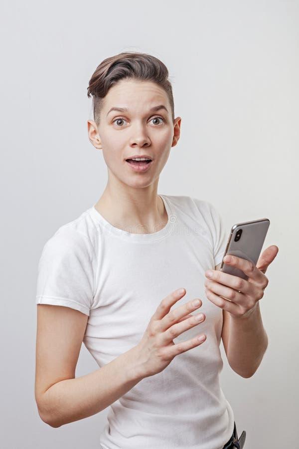 Выигрыш счастливой смешной тысячелетней женщины празднуя или победа, триумф, держа телефон Жизнерадостная возбужденная девушка, с стоковые фотографии rf
