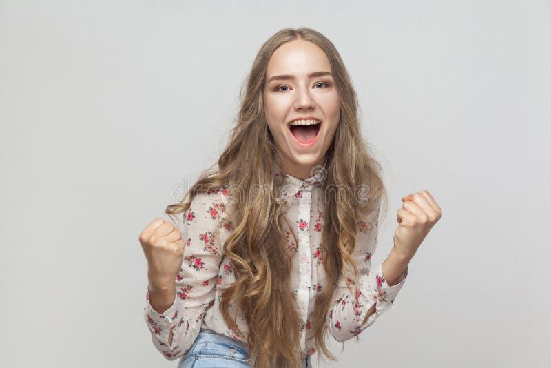Выигрыш! Эмоциональный белокурый окрик женщины и имеет взгляд счастья и стоковые фото