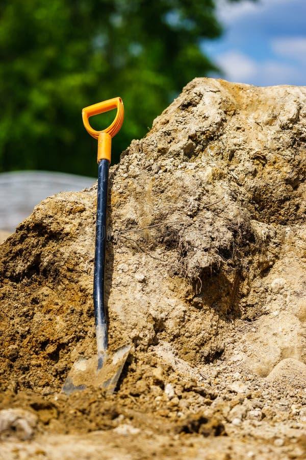 Выкапывать с лопаткоулавливателем Лопаткоулавливатель основанный на куче земли стоковое фото