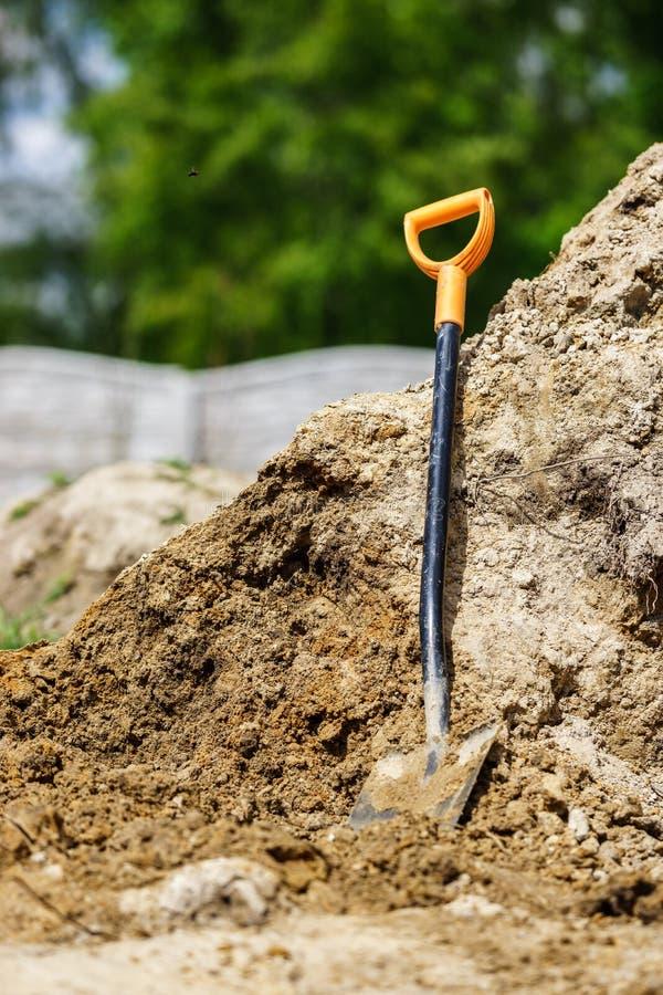 Выкапывать с лопаткоулавливателем Лопаткоулавливатель основанный на куче земли стоковое изображение