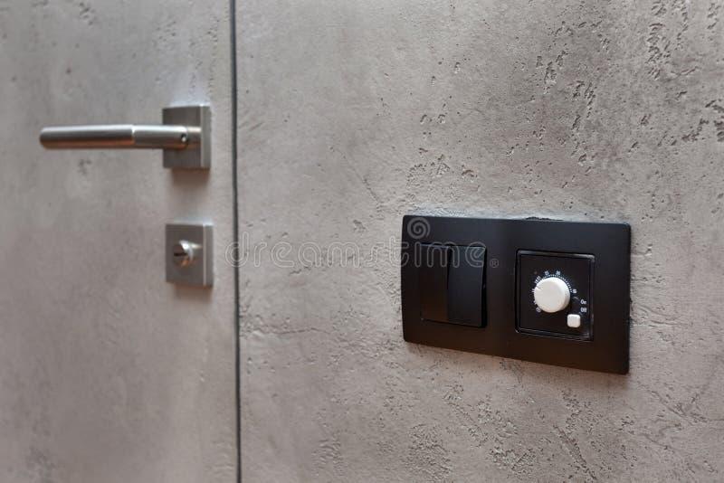 Выключатель на серой текстурированной стене рядом с дверью с металлической ручкой стоковое фото rf