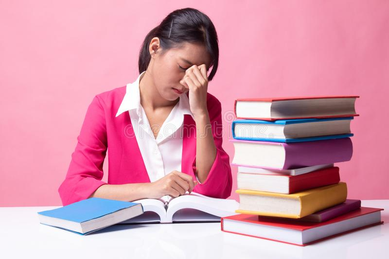 Вымотанная азиатская женщина получила головную боль прочитала книгу с книгами на таблице стоковое фото rf