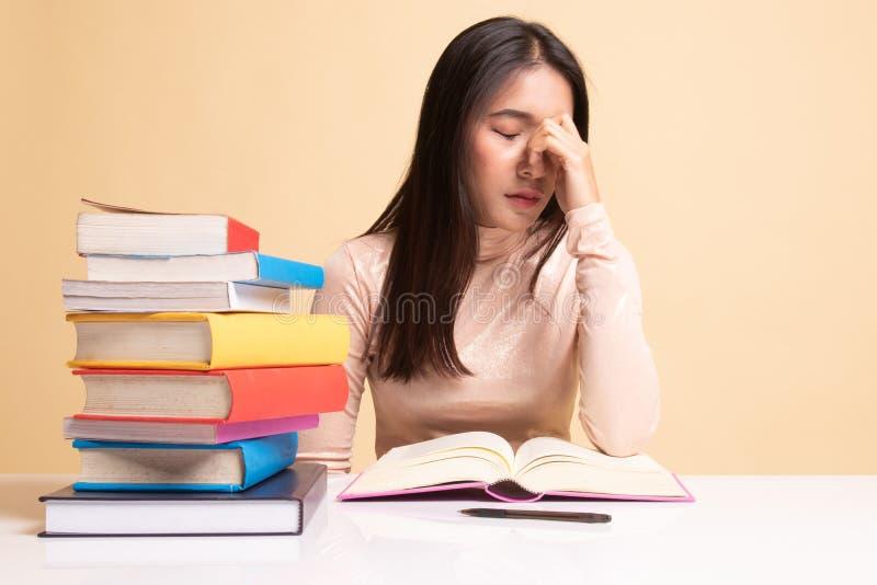 Вымотанная азиатская женщина получила головную боль прочитала книгу с книгами на таблице стоковые фотографии rf