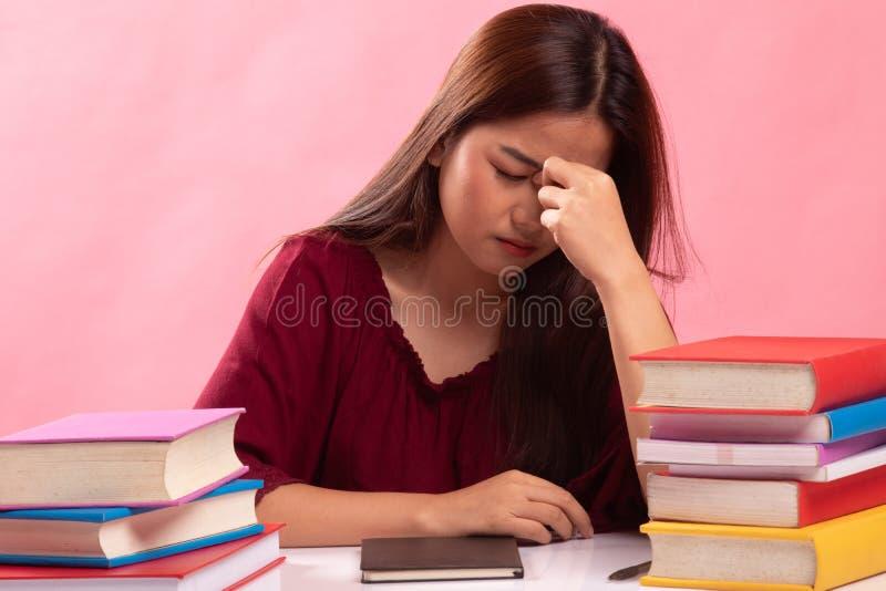 Вымотанная азиатская женщина получила головную боль прочитала книгу с книгами на таблице стоковые фото