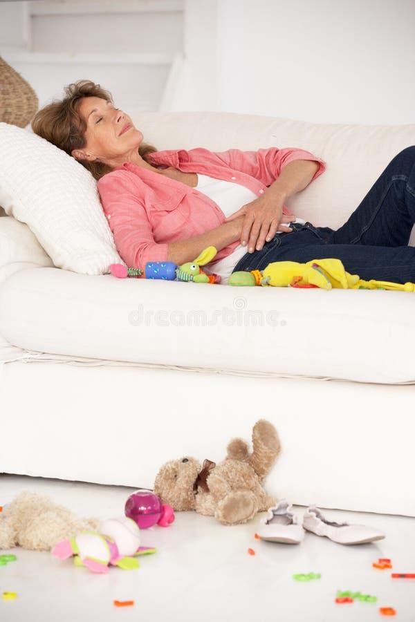 Вымотанная бабушка наслаждаясь остальными на софе стоковые фото