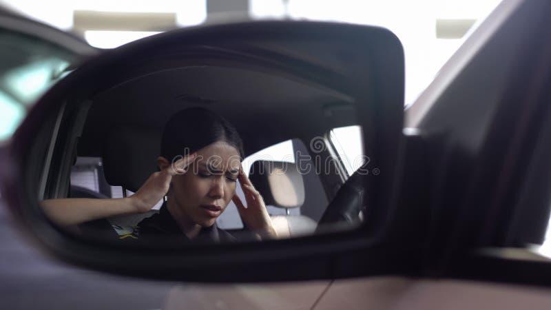 Вымотанная головная боль чувства женщина-полицейского массажируя виски, усиленную работу, занятую стоковая фотография rf
