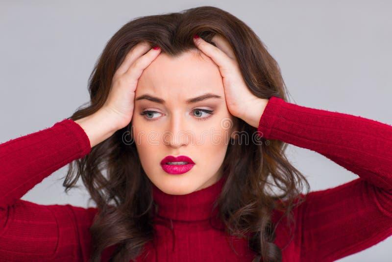 Вымотанная женщина касаясь ее голове стоковая фотография