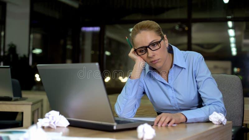 Вымотанная женщина нуждаясь идеях дела, работая часах в офисе, прогар стоковая фотография rf