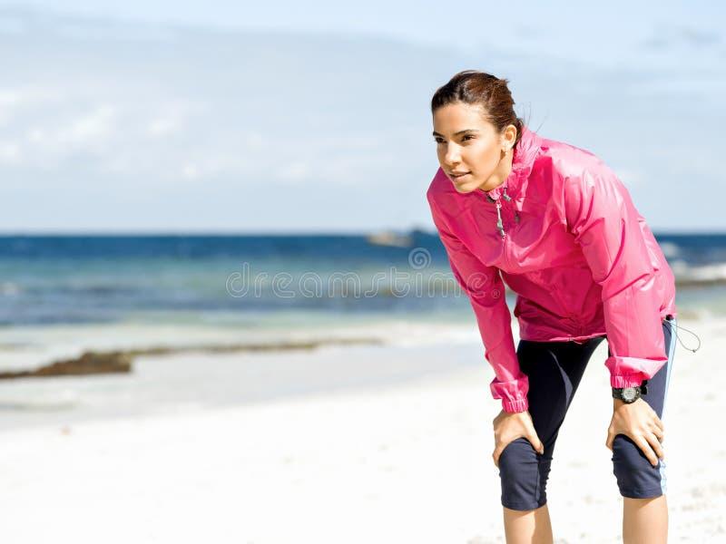 Вымотанная женщина фитнеса принимая пролом после бежать стоковая фотография rf