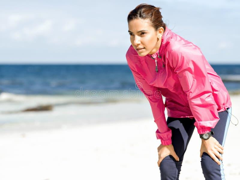 Вымотанная женщина фитнеса принимая пролом после бежать стоковые фотографии rf