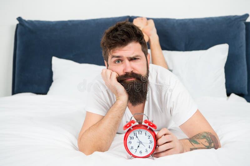 Вымотанное чувство уставший бородатый хипстер человека с будильником зверский сонный человек в спальне контроль времени зрелый стоковое фото