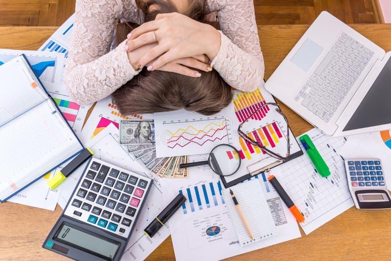 Вымотанный аналитик деловой активности спит на ее рабочем месте стоковая фотография