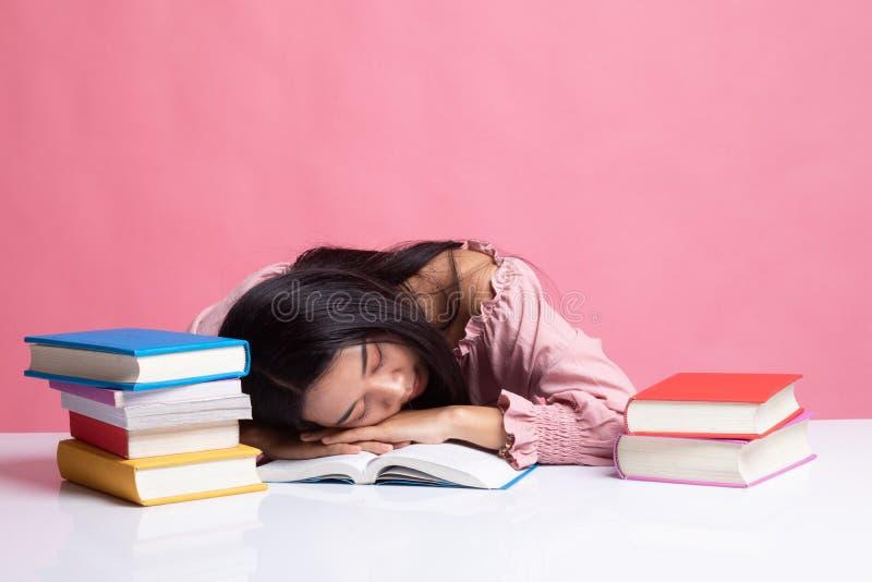 Вымотанный молодой азиатский сон женщины с книгами на таблице стоковая фотография rf