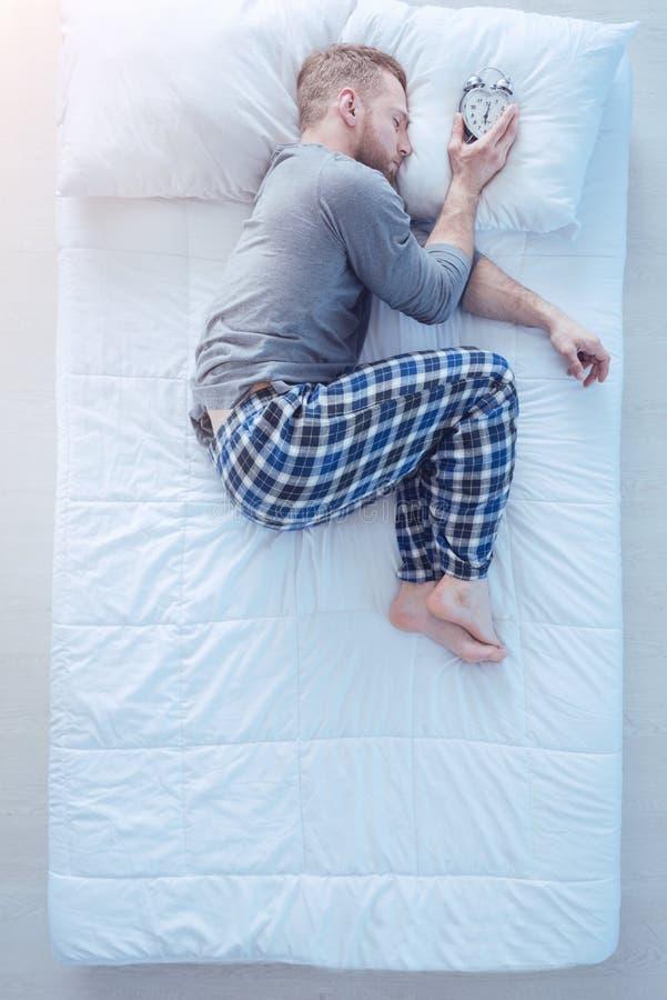 Вымотанный парень держа будильник пока спящ стоковое изображение
