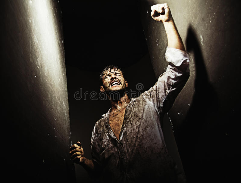 Вымотанный победоносный человек после грубого выживания стоковое фото