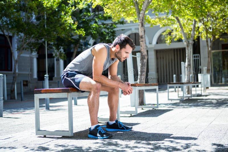 Вымотанный спортсмен отдыхая на стенде стоковые фотографии rf
