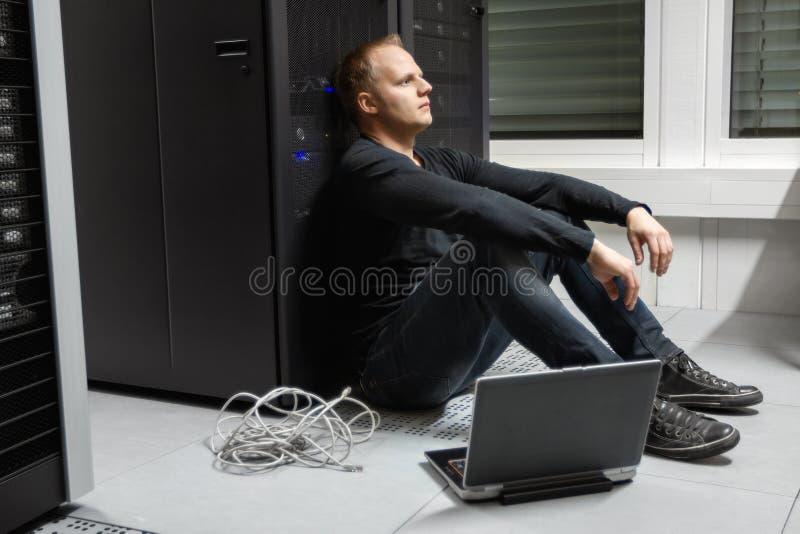 Вымотанный средний техник взрослого мужчины против шкафа сервера на Datacenter стоковое изображение rf