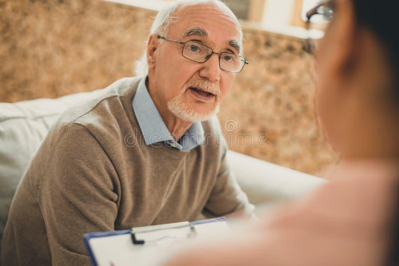 Вымотанный старший с белой бородой спрашивая его волонтеру стоковые фотографии rf