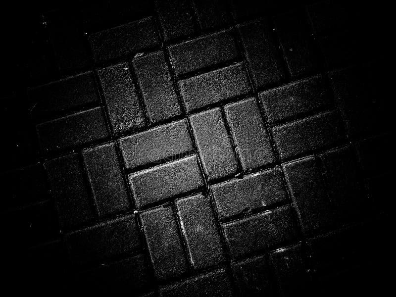 Вымощать черную предпосылку текстуры фона цвета стоковое фото