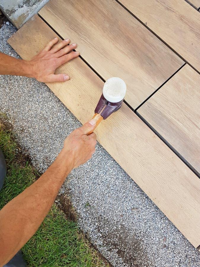 Вымощающ патио - приспособление каменной плитки с резиновым мушкелом стоковая фотография