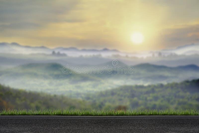 Вымощенная дорога с восходом солнца зимы взгляда нерезкости туманным в предпосылке гор естественной стоковые фотографии rf