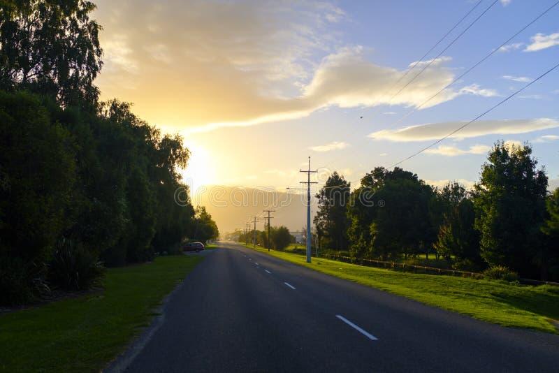 Вымощенная дорога с заходом солнца на заднем плане стоковые изображения